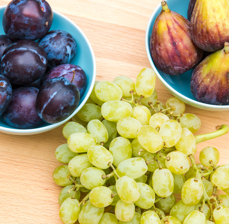 Plums, figs and white grapes on wooden board. photo