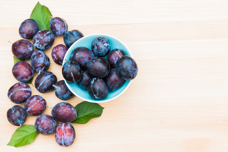 Fresh ripe plums on wooden board with copyspace. photo