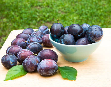 Fresh ripe plums in  bowl. Selective focus photo