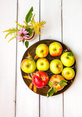 Plate of variates of fresh apples including jonagold and mutsu  and a vase with wildflowers on wooden table, autumn still life. photo