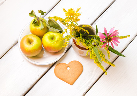 Plate of fresh  jonagold  apples, heart shaped cookie and  vase with wildflowers on wooden table, autumn still life. photo