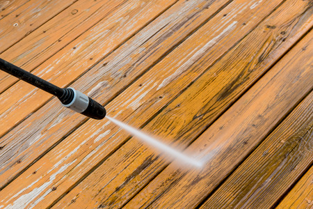 power tool: Power washing. Wooden deck floor cleaning with high pressure water jet.