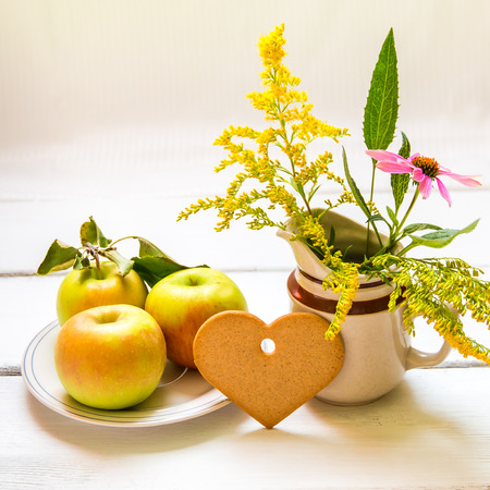 Plate of fresh apples, heart shaped cookie and  vase with wildflowers on wooden table, autumn still life. Shallow DOF. photo