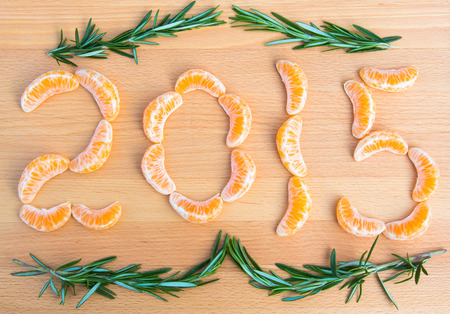 sprigs: 2015 number written with oranges sections and rosemary sprigs on wooden background Stock Photo