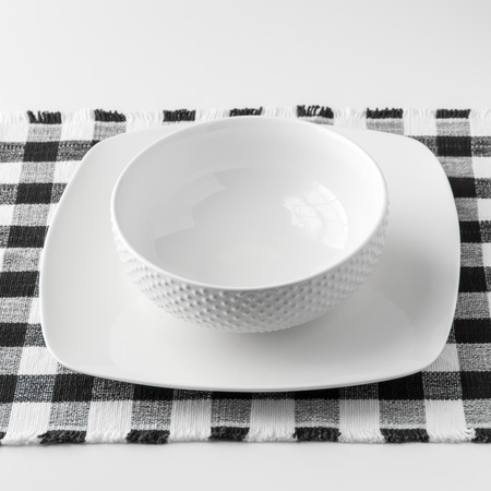 checked fabric: Empty white bowl and plate on checked fabric placemat