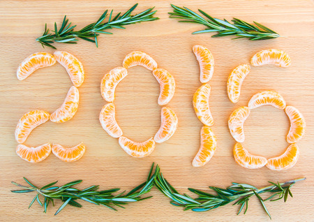 sprigs: 2016 number written with oranges sections and rosemary sprigs on wooden background
