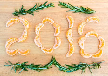owoców: 2016 Numer napisany z pomarańczy sekcjach i gałązki rozmarynu na drewnianym tle