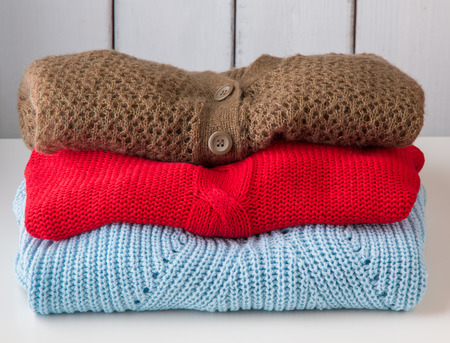 cable stitch: Stack of womens knitted sweaters and cardigans.