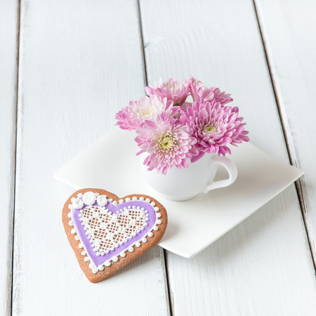 beautiful anniversary: Cup full of pink  mum flowers and  heart shape cookie on white wooden table.