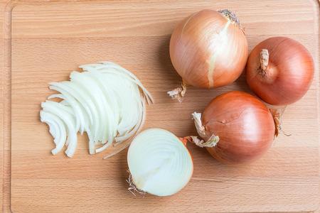 cebolla: Cebollas enteras y en rodajas en tabla de cortar de madera. Foto de archivo