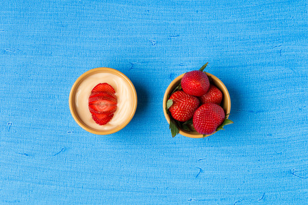vanilla pudding: Vanilla pudding and strawberries in small  bowls on blue background. Stock Photo