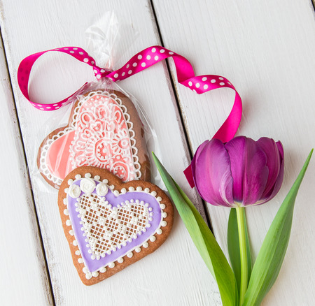 Heart shaped cookie decorated with ornaments and flowers for Valentines day.