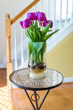 vase: Purple tulips in a vase on mosaic table in hall near front door and stairway.
