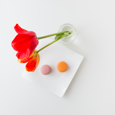 Two tulip flowers in glass vase and two macaroon cookies on a plate, top view. Stock Photo