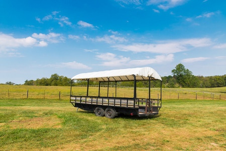 Covered wagon with white top in farm fields.