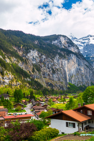 Swiss Alps and green fields in famous touristic town with high waterfall in background. Lauterbrunnen, Switzerland,Europe. Stock Photo