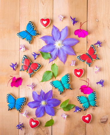 clematis: Colorful flowers and homemade butterfly shaped cookies floral composition on cedar wood table. Stock Photo
