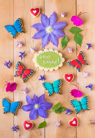 clematis: Colorful flowers, homemade happy birthday cookie and butterfly shaped cookies composition  on cedar wood table.
