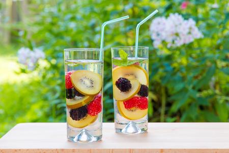 Dois copos de deliciosa bebida refrescante. Água infundida com bagas, kiwi dourado e hortelã.