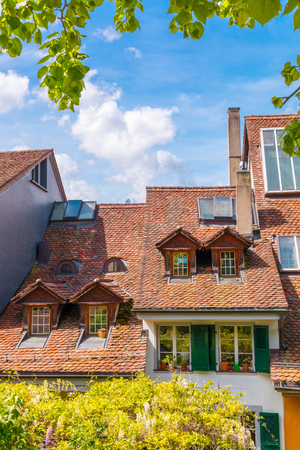 View of red tile roofs and dormer windows on old historical houses in  Thun city, Switzerland.