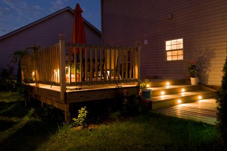 Terrasse en bois et patio de la maison familiale la nuit.