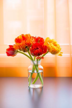 Beautiful tulips bouquet in vase on table near window.