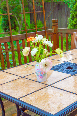 Bouquet of ranunculus flowers on garden table on rainy day. 免版税图像