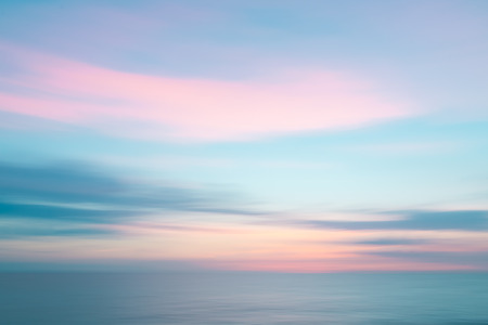 Abstract colorful sunset sky and ocean nature background with blurred panning motion.