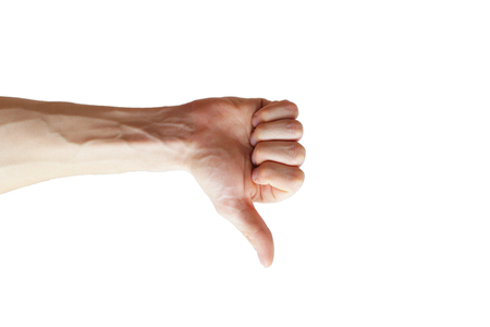 Closeup of male hand showing thumbs down sign against white background