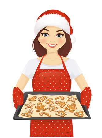 Smiling woman holding baking tray with christmas cookies wearing santa hat isolated