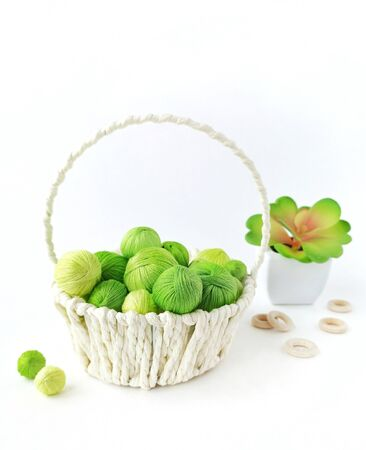 White basket with green yarn for knitting. Threads for needlework.