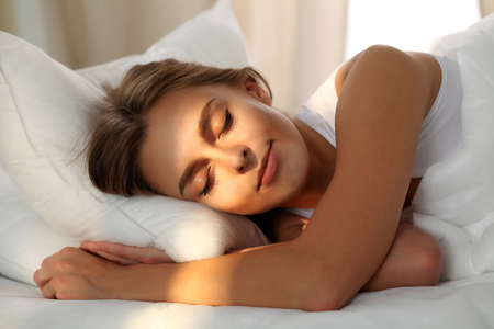 blissfully: Beautiful young woman sleeping while lying in bed comfortably and blissfully. Sunbeam dawn  on her face