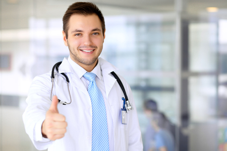 Smiling doctor waiting for his team while standing upright. Thumbs up