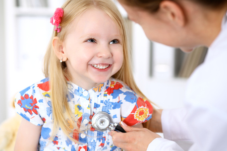 Pediatrician is taking care of baby in hospital. Little girl is being examine by doctor by stethoscope. Health care, insurance and help concept. Stock Photo
