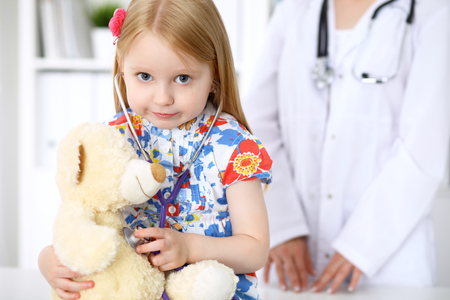 Little girl examining her Teddy bear by stethoscope. Health care, child-patient trust concept