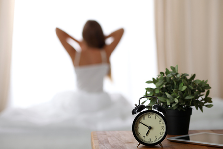 Alarm clock standing on bedside table has already rung early morning to wake up woman in bed sitting in background. Early awakening, not getting enough sleep, oversleep, time line concept. 版權商用圖片