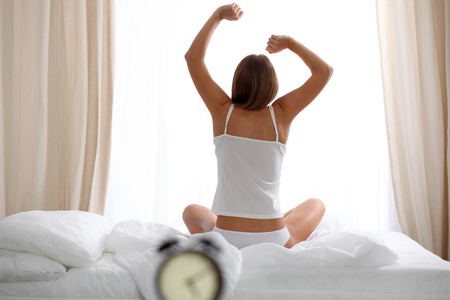 Woman stretching in bed after wake up, back view, entering a day happy and relaxed after good night sleep. Sweet dreams, good morning, new day, weekend, holidays concept. Stock Photo