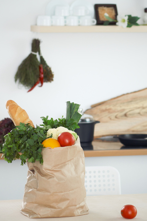 Paper bag full of vegetables on the table in kitchen interiors. Healthy meal and vegetarian concept.