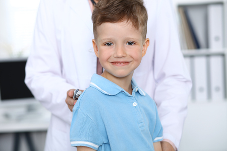 Doctor and patient in hospital. Happy little boy having fun while being examined with stethoscope. Healthcare and insurance concept Reklamní fotografie