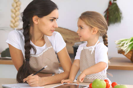 Happy family in the kitchen. Mother and child daughter make menue for cooking tasty breakfest in the kitchen. Little helper is ready for houshold job
