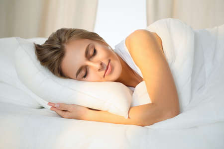 Beautiful young woman sleeping while lying in bed comfortably and blissfully Sunbeam dawn on her face