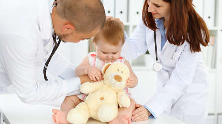 Happy smiling girl-child at usual medical inspection. Doctor and female toddler patient in the clinic. Medicine, healthcare concepts Standard-Bild