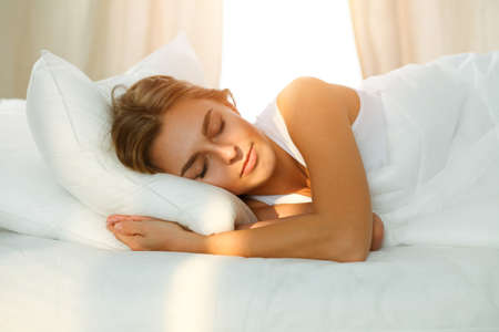 Beautiful blonde girl sleeping sweetly in sunny bedroom on a white bed. Holyday comfort and Rest concepts