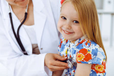 Happy smiling girl at usual medical inspection. Doctor and patient in clinic. Medicine, healthcare concepts