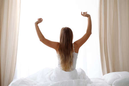 Woman stretching in bed after wake up, back view, entering a day happy and relaxed after good night sleep. Sweet dreams, good morning, new day, weekend, holidays concept Stock Photo