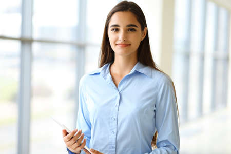A friendly young businesswoman or female student is standing with some papers in the office. Lifestyle and diverse people concept