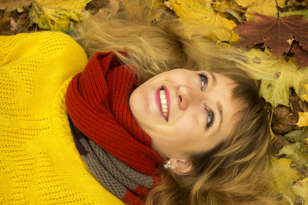 lying on leaves: Young beautiful girl lying on autumn leaves and smiling