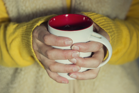 to get warm: Soft and blur conception.A woman holds a hot cup of tea and warms his hands
