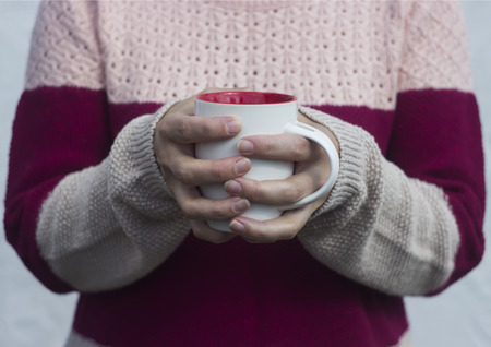 to get warm: A woman holds a hot cup of tea and warms his hands