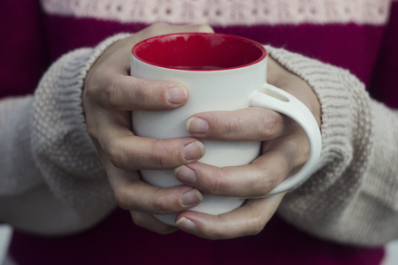 warms: Soft and blur conception.A woman holds a hot cup of tea and warms his hands